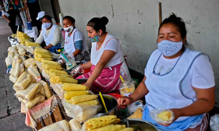 Women wearing face masks sell corn cobs outside the market in Xochimilco, Mexico City