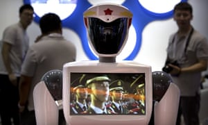 A video screen plays footage of Chinese People's Liberation Army soldiers on a robot