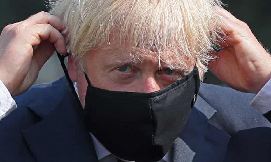Boris Johnson puts on a black mask.