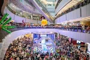 Hong Kong, China: On a screen in a shopping mall, people watch Siobhan Bernadette Haughey of Hong Kong swim in the women's 100m freestyle final at the 2020 Summer Olympics