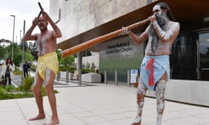 Aboriginal dancers perform outside the inquest before it began on Monday