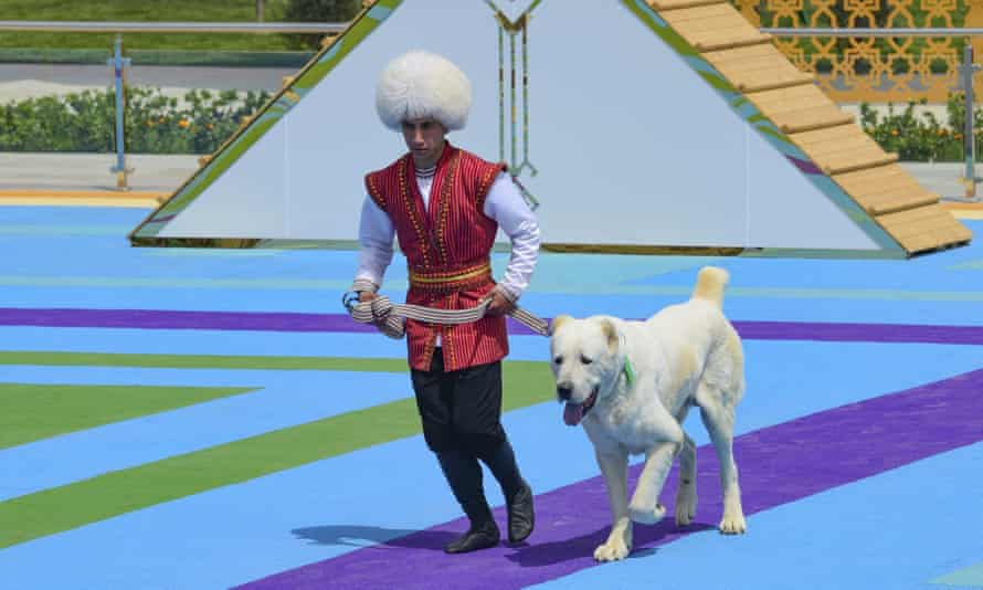 A man dressed in a national costume runs with his border guard shepherd dog Alabai during Dog Day celebration in Ashgabat, Turkmenistan, Sunday, 25 April 2021.