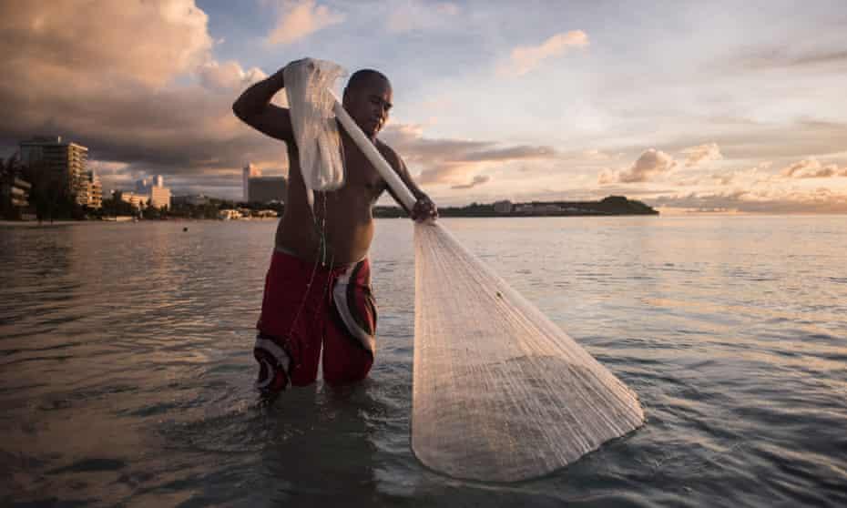 A fisherman catches 'goat fish' off a beach in Guam.