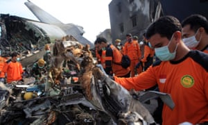 Indonesian rescuers examine the wreckage of the crashed C-130 military airplane as they search for victims at the crash site in Medan.