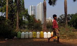 A boy walks past containers filled with drinking water at a tribal settlement in Mumbai