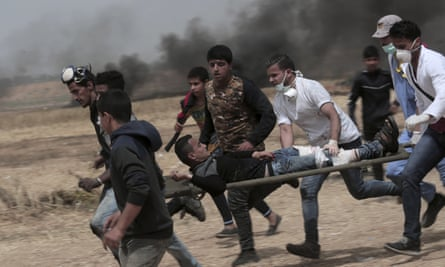 A wounded youth is carried on a stretcher by running men