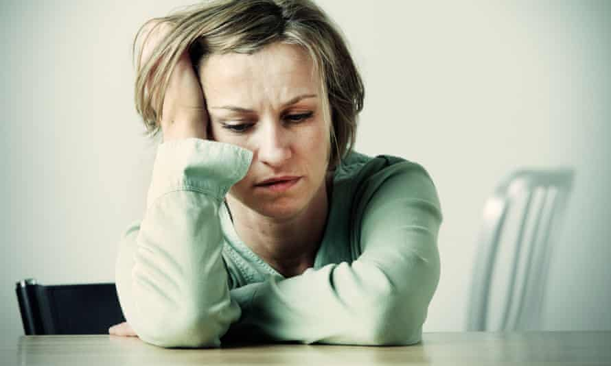 Woman holding head in hands at desk<br>