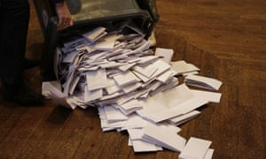 an official empties a wheelie bin full of ballot papers on to a parquet floor