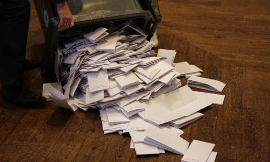 an official empties a wheelie bin full of ballot papers on to a parquet floor