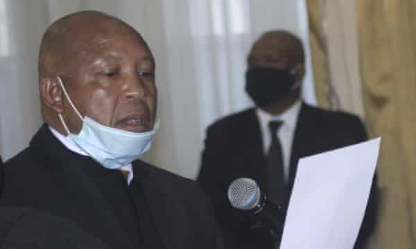 Moeketsi Majoro in mask reading from A4 paper.