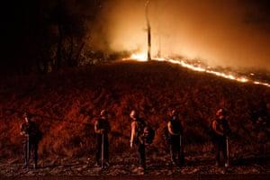 Firefighters stand watch by a fire line along Mayacama Club Drive.