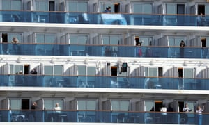 Passengers of the Diamond Princess cruise ship gesture from their balcony