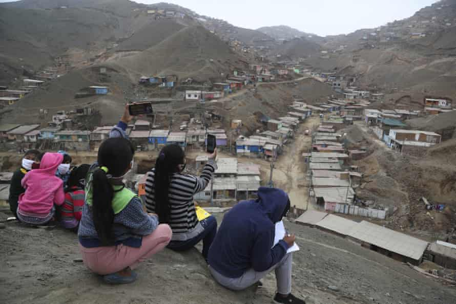 Children raise their phones to try to get a mobile signal during virtual classes in the Puente Piedra shantytown outside Lima.