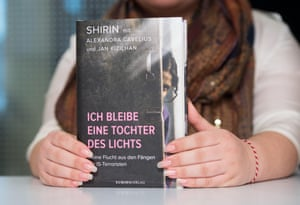 The Yazidi author, writing under her pseudonym Shirin, holds her new book in her hands, titled 'Ich bleibe eine Tochter des Lichts' (I remain a daughter of light), during a book presentation in Munich