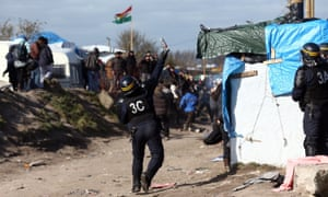 A police officer throws teargas as part of the 'jungle' migrant camp is cleared.