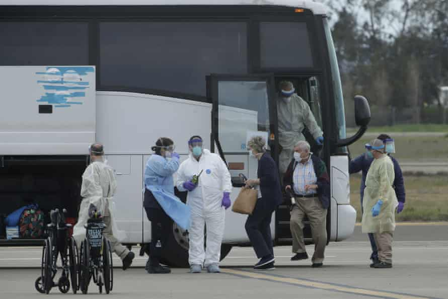 Passengers from the Grand Princess cruise ship exit a bus before boarding a chartered flight to San Antonio, Texas.