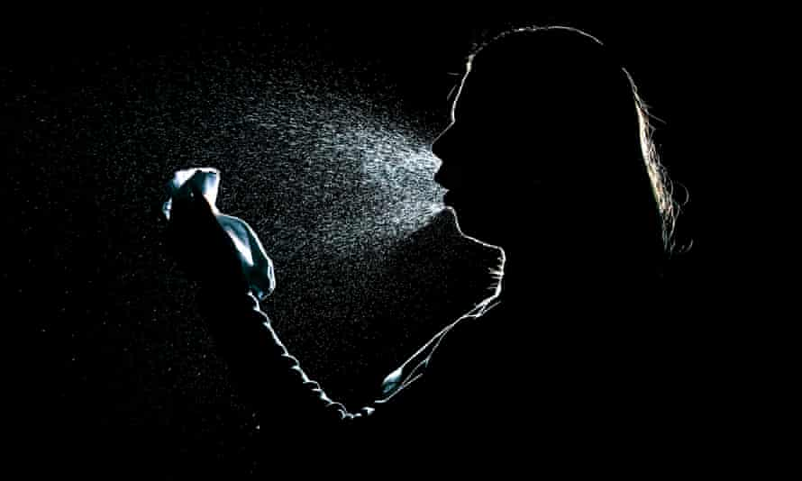 Silhouette of a woman sneezing and spreading virus droplets in the air
