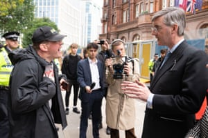Dominic Hutchins (left) confronting Jacob Rees Mogg outside the conference today.