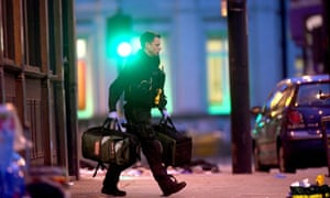 An armed police officer recovers medical bags at the scene in Streatham High Road, south London, after a man was shot dead by armed officers