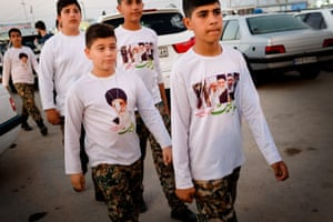 Children arrive by bus at the memorial site. They are wearing T-shirts bearing the portraits of Ayatollah and martyrs