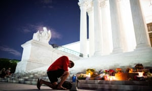 A man kneels as he brings a megaphone to a vigil on the steps of the US supreme court.