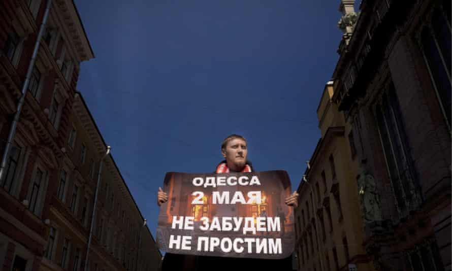 A lone protester walks through the city centre.