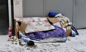 cardboard box and sleeping bag on snow-covered street in Windsor, Berkshire