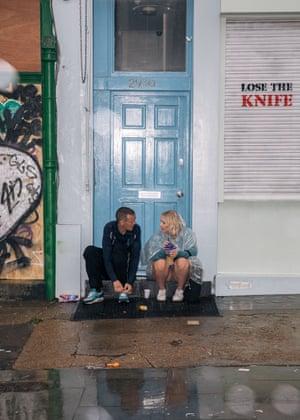 Two people take a break from the rain on Portobello Road.