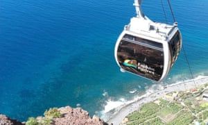 The new cable car at Fajã dos Padres. A car, viewed from above, makes its way down the cliff to the coast and blue sea shore below.
