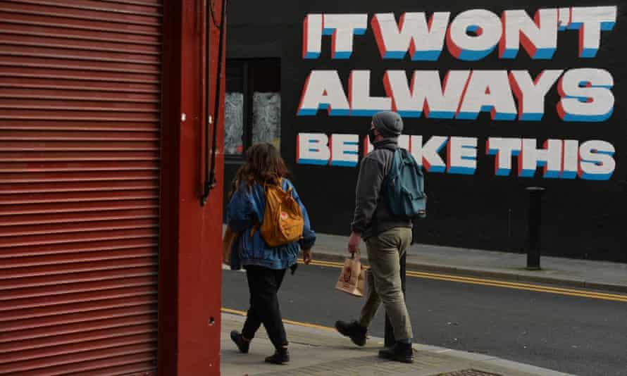People walk past a mural by the Irish artist Emmalene Blake in Dublin's city centre.