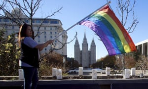 Sandy Newcomb stands with a flag near the Salt Lake Temple.