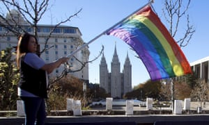 Sandy Newcomb waves a flag near the Salt Lake Temple after members of the Church of Jesus Christ of Latter-day Saints mailed their membership resignations in Salt Lake City on Saturday.