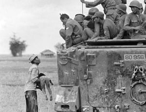 A distraught father holds the body of his child as South Vietnamese Rangers look down from their armoured vehicle, March 19, 1964