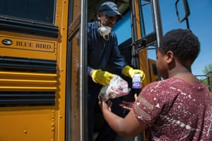 Robert King, transportation supervisor for Holmes County Consolidated School District, delivers school lunches to student Keizarrian Thomas, in Lexington, Mississippi, on April 1, 2020.