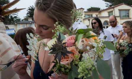 A bridesmaid holds a bouquet containing cannabis buds