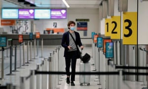 A passenger wearing a face mask arrives at the check-in counters at an almost empty Gatwick Airport, amid the coronavirus disease (COVID-19) outbreak.