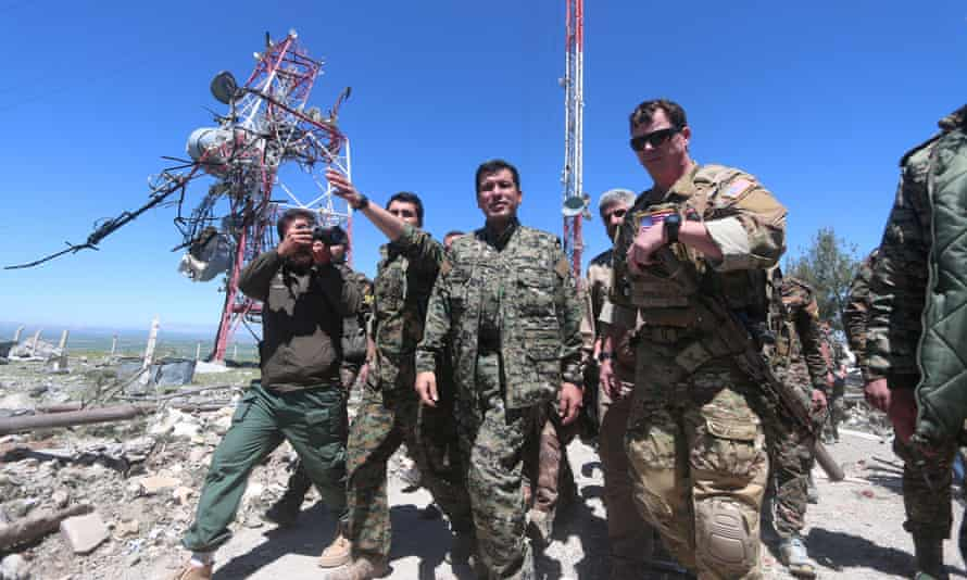 A US military commander inspects the damage from Turkish airstrikes last week with a commander from the Kurdish YPG in Mount Karachok, Syria.