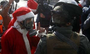 A Palestinian protester dress up like Santa Claus argues with Israeli security forces at the separation wall in Bethlehem.