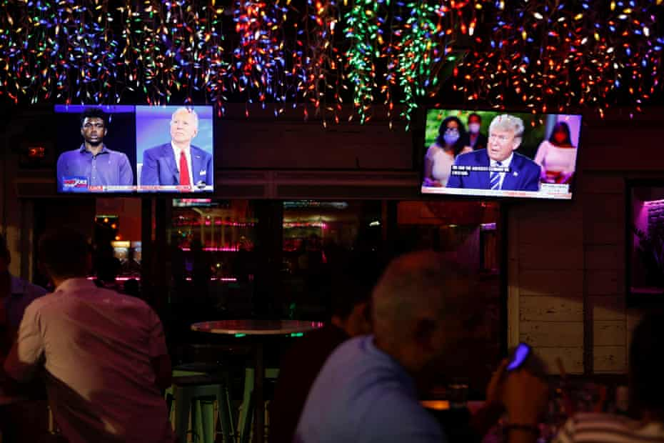 The dual town halls are seen on television monitors at Luv Child restaurant ahead of the election in Tampa, Florida, on Thursday night.