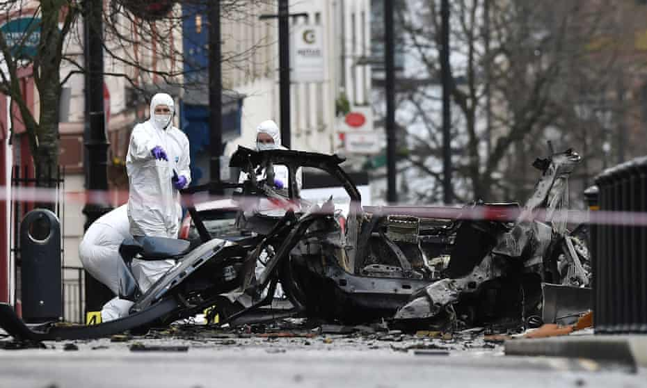 Forensic officers inspect the remains of the vehicle used in the bombing outside a courthouse in Derry