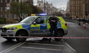 An armed police officer gets out of a car inside a police cordon outside the Houses of Parliament