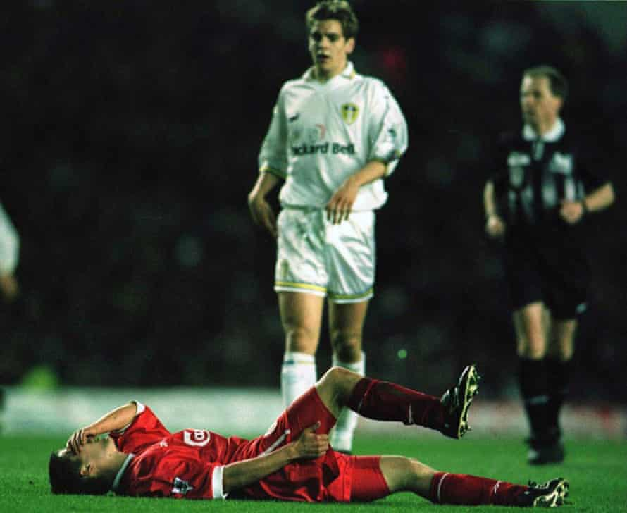 Michael Owen holds his leg in pain.