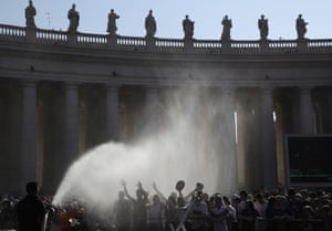 Rome, Italy A firefighter cools off the faithful waiting for Pope Francis in St. Peter's square at the Vatican