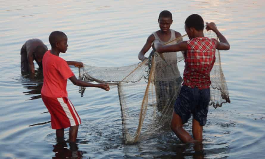 """Boys fish in waters near Barra Vieja, on the northern coast of Honduras. """"We Garifunas are being persecuted by the government to evict us from our land for their touristic developments, which aren't for the benefit of our communities,"""" said José Guzmán Niri, from the Barra Vieja Garifuna community."""