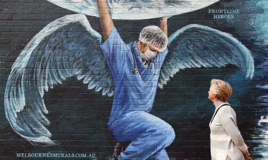 A woman looks at a mural of a health worker