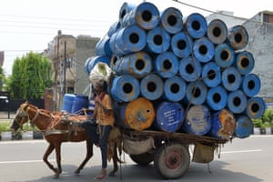 A horse pulls a cart stacked with empty container drums in Amritsar, India