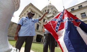 Mississippi state employees Willie Townsend, left, and Joe Brown raise the state flag over the Capitol grounds.