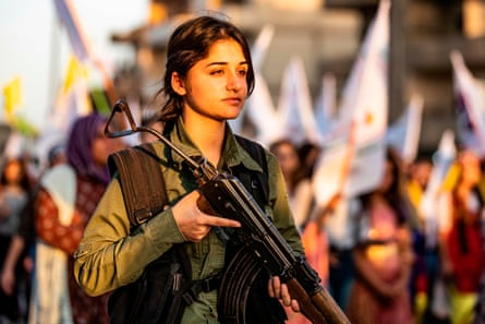 A Kurdish security officer stands guard at a rally against Turkish threats to invade the region in Qamishli in August.