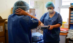 Intensive care staff put on personal protection equipment (PPE) before entering a Covid-19 unit