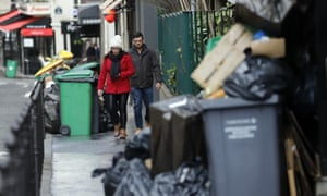 People walk past piles of rubbish amid strikes over changes to France's national retirement system that have disrupted a key incineration plant.